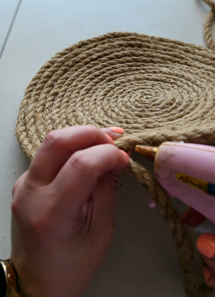 Adding hot glue to the edges of the rope, while rolling it to a flat circle.