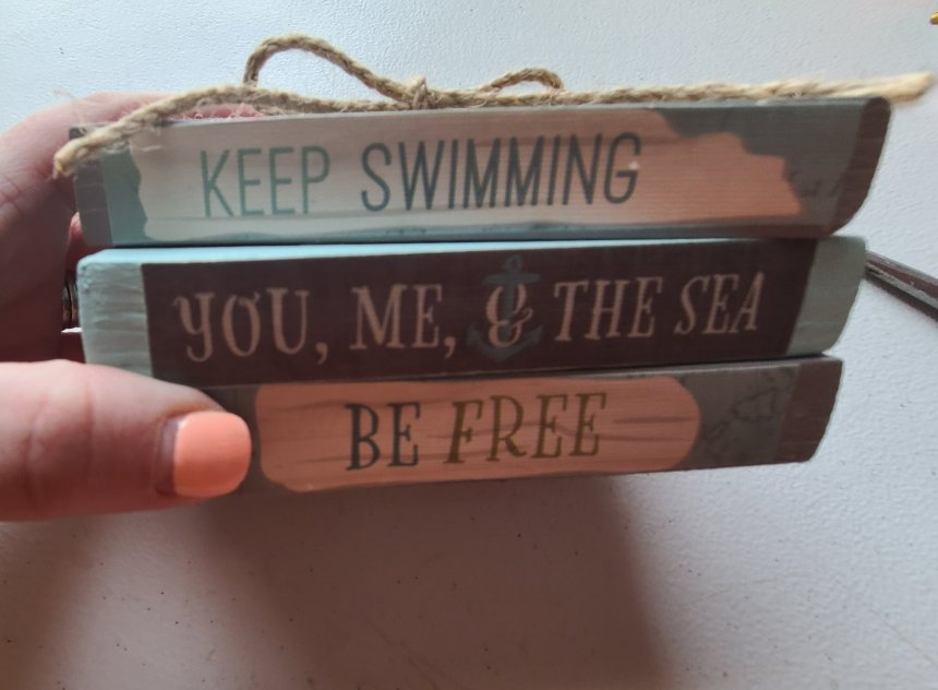 Three wood blocks made to look like books with beachy titles, wrapped with jute rope twine.