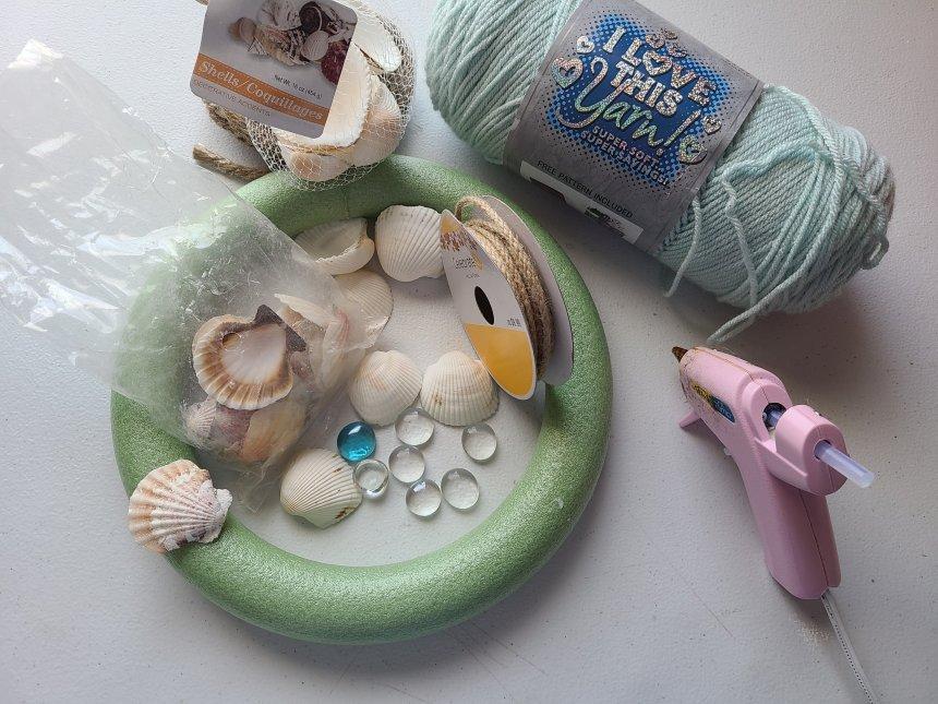 Supplies needed for a beach wreath: seashellls, twine, nautical rope, robin's egg blue yarn, hot glue gun.