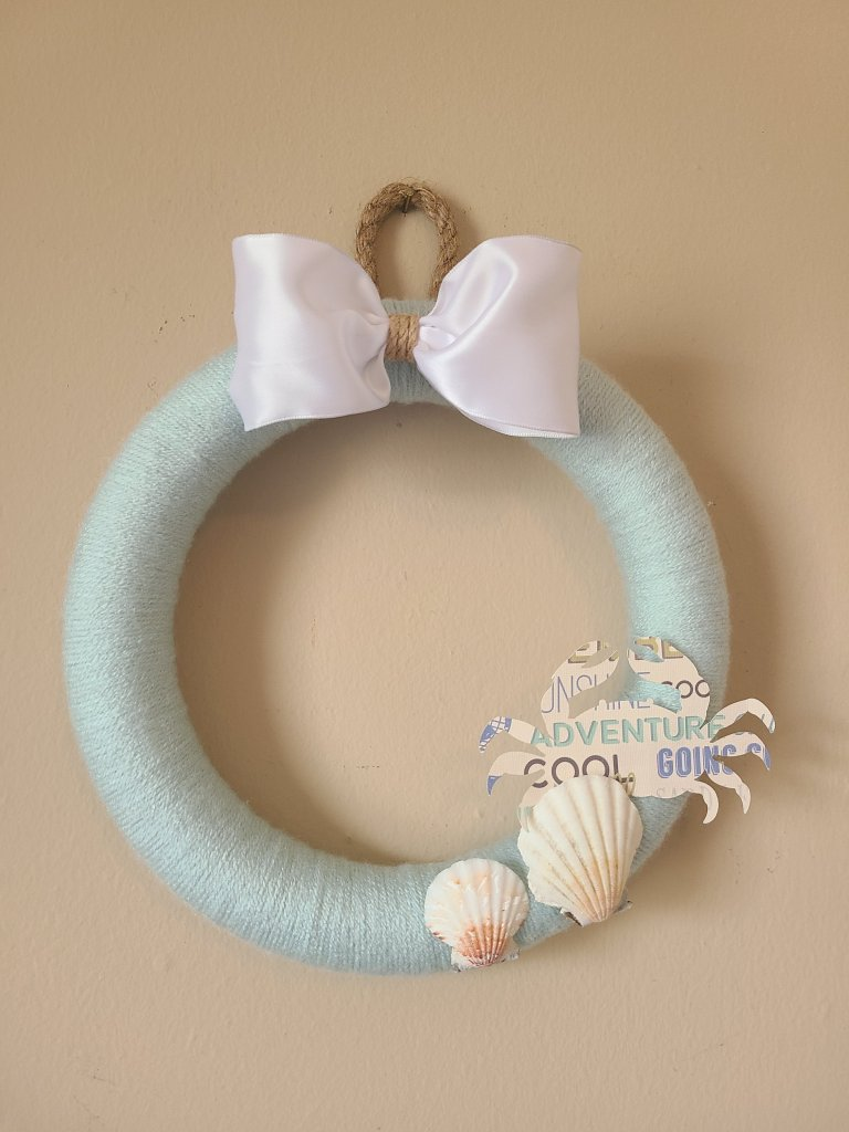 DIY Yarn wreath made with light robin's egg blue yarn, seashells, a white bow, and nautical rope.
