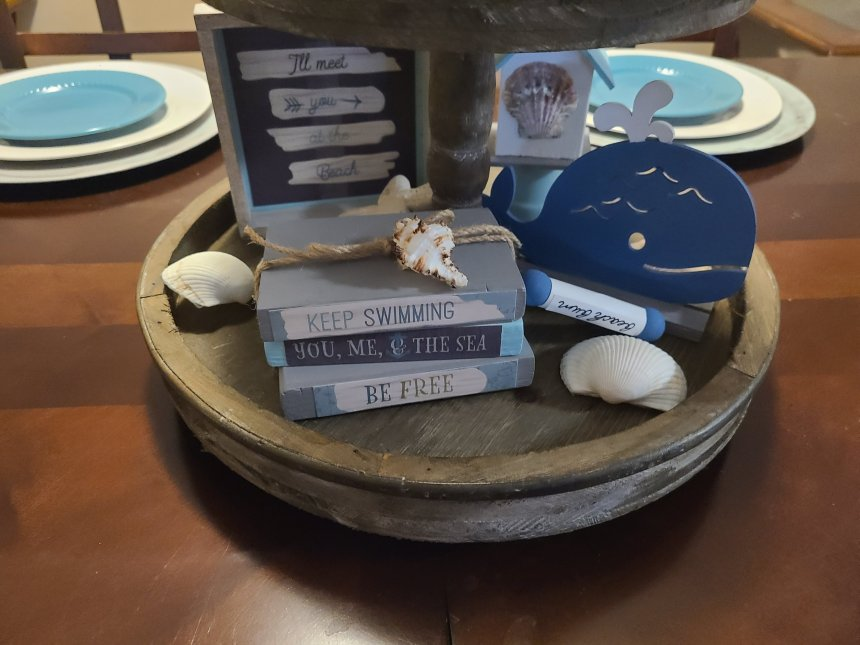 Faux books, seashells, blue wood whale, and a seashelled birdhouse on the bottom of the beach themed tiered-tray.