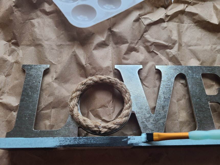 Galvanized metal letters spelling LOVE being painted with robin's egg blue acrylic paint. Nautical rope is used to make the O, to make a beach table-top sign.