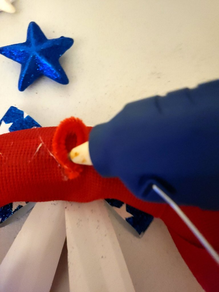 Red pipe cleaner twisted to form a loop and being hot glued to the back of the DIY patriotic wreath.