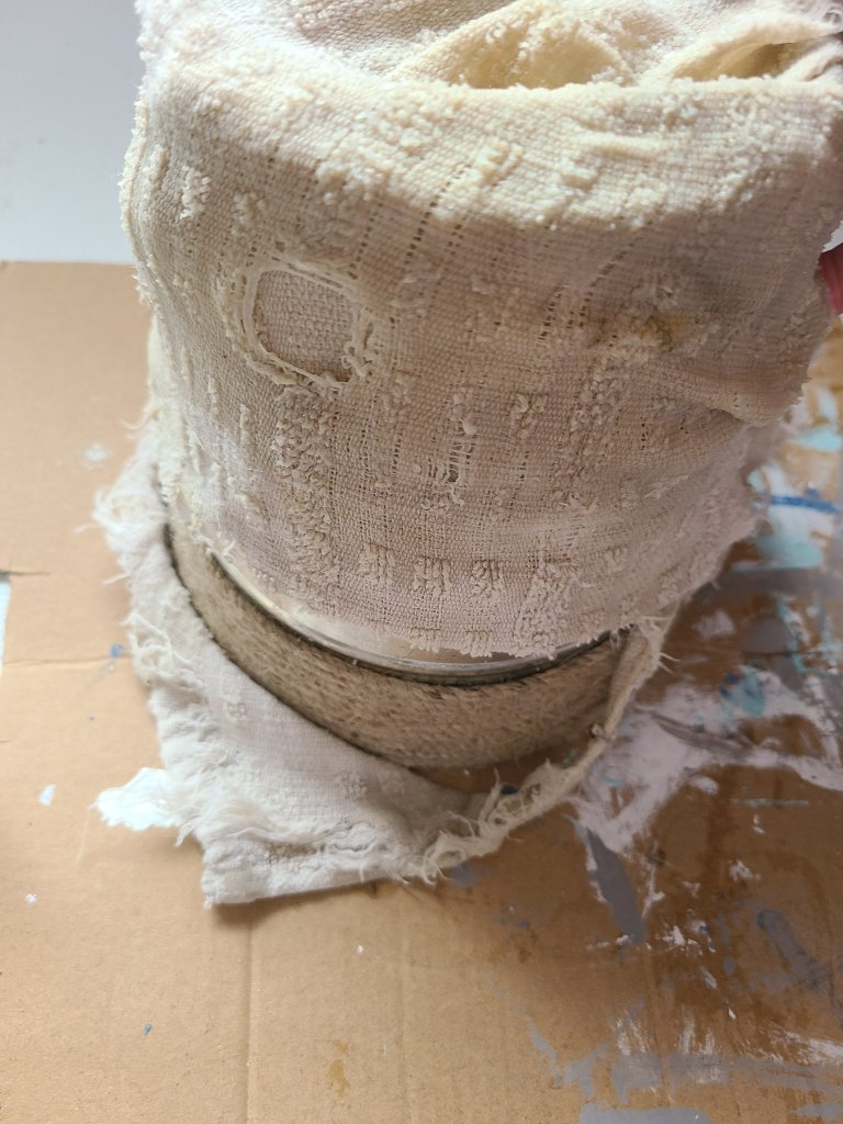 Rag soaked in peroxide, vinegar, and salt wrapped around a metal flower pot to create a DIY aged metal farmhouse flower pot.