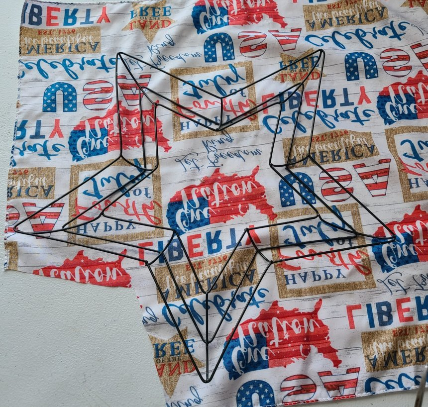 White bandana with patriotic red and blue shapes and phrases with a star shaped wire wreath form on top. A section of the fabric has been cut away to size to form a patriotic star wreath.
