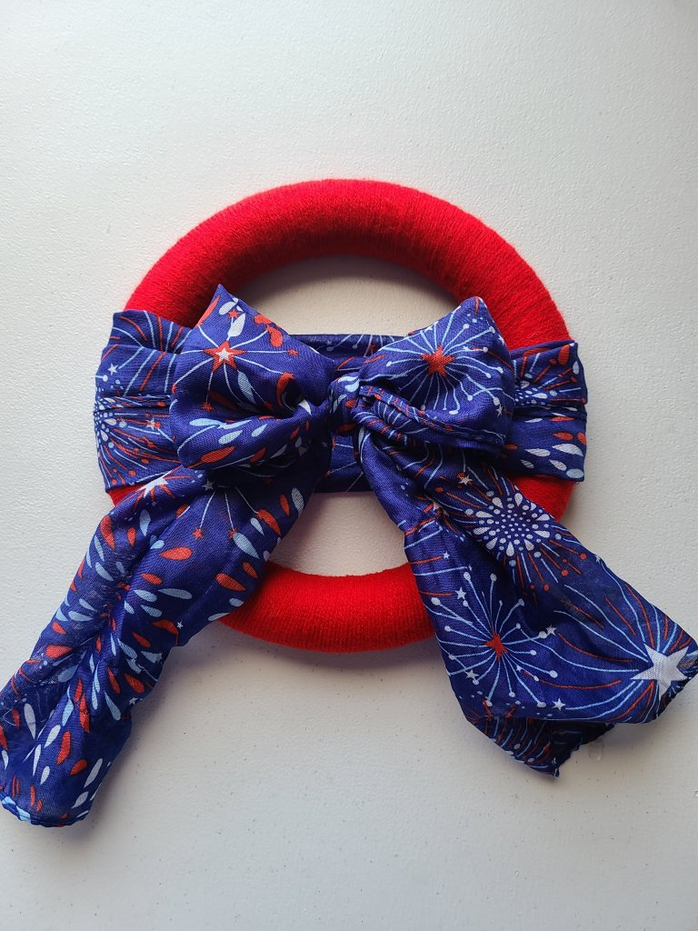 Scarf and yarn patriotic wreath- red yarn wrapped wreath form, blue scarf wrapped around the middle and tied in a bow with the bow in the middle of the wreath
