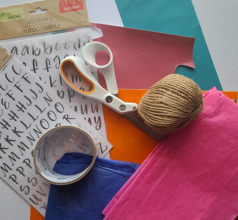 Items to personalize summer camp care package: scissors, twine, blue and pink tissue paper, pink and orange vinyl, white and blue cardstock, and letter stickers.