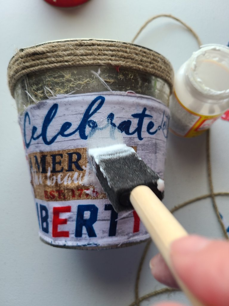 Using a foam brush to add a layer of Mod Podge on top of the fabric scraps on the patriotic centerpiece.