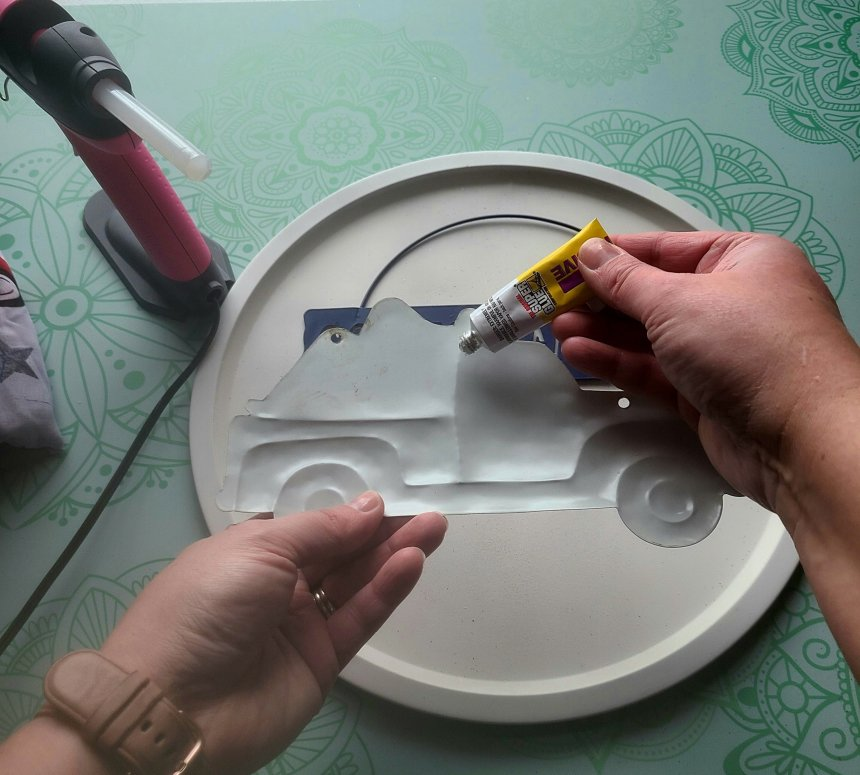 Add liquid adhesive to the back of the metal truck sign and press it on to the patriotic pizza pan wreath.