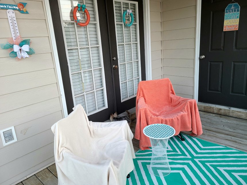 """Summer porch re-do for under $20. DIY side table made with two white wire trash cans & a pizza pan top, teal & white outdoor rug under that & two chairs, one white & one coral. Outdoor thermometer hanging on the siding with a wood arrow top saying """"beach this way."""" Beach sign on a door that says """"salt in the air, sand in my hair"""" that is blue, teal, yellow, & coral. Two wreats hanging on French doors, one coral with teal bow & starfish & one teal with coral starfish & white bow."""