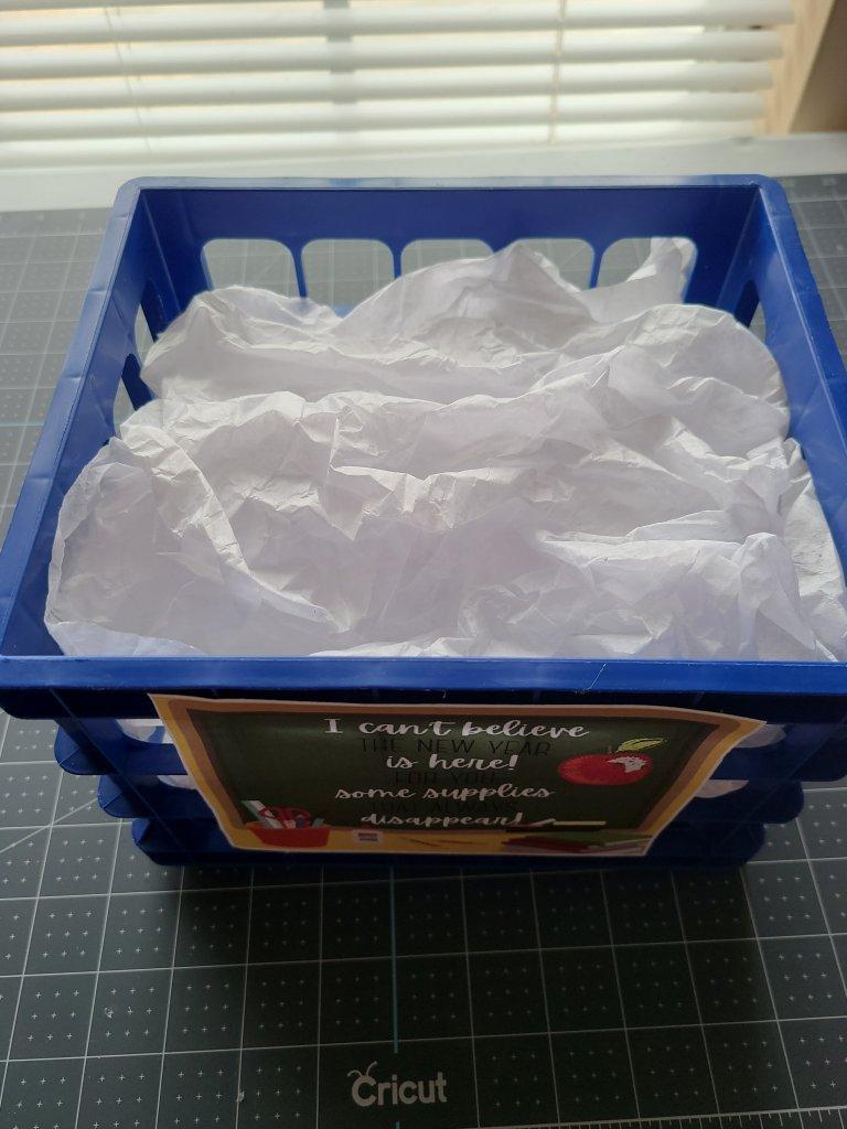 White tissue paper filling blue back to school teacher's gift basket.