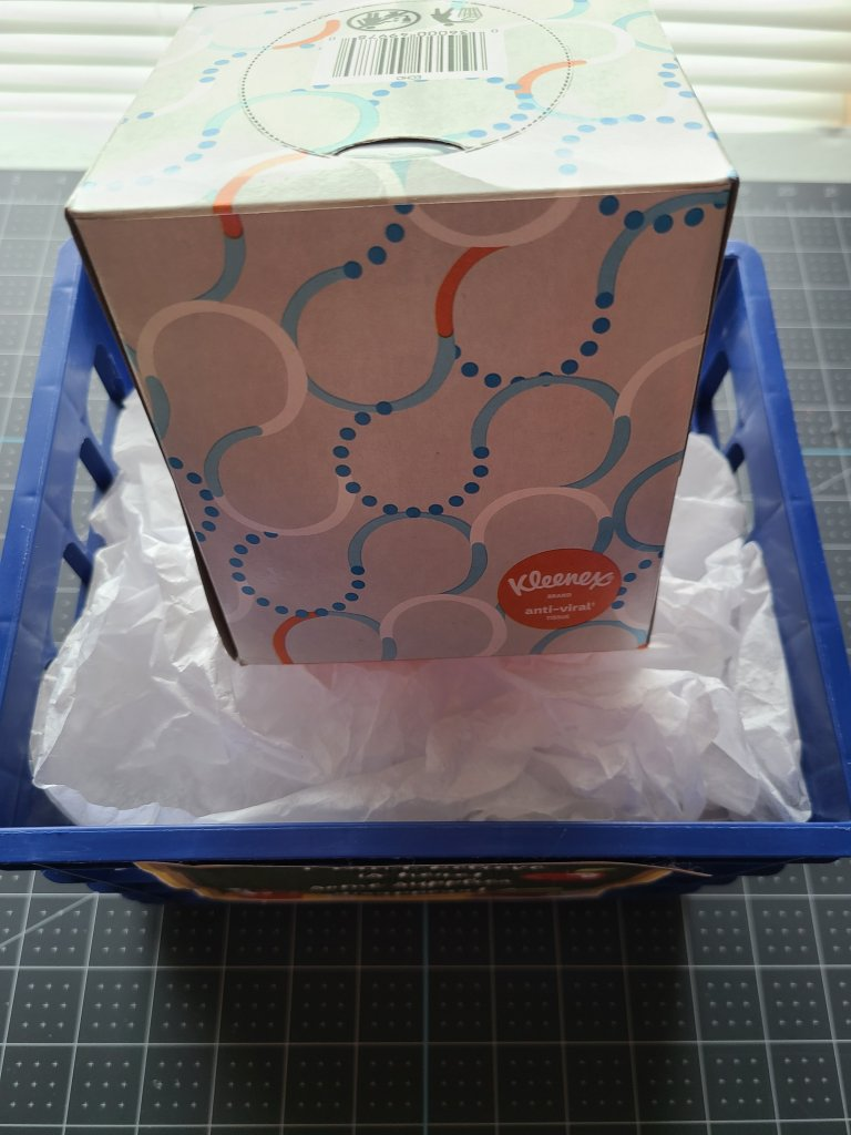 Box of Kleenex on top of white tissue paper in blue bin