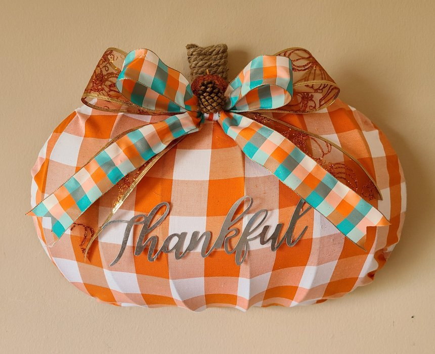 Orange and white buffalo check pumpkin wreath with gold and orange glitter bow with an orange, aqua, and white plaid bow on top of it. The stem is created with nautical rope and the bows have a tiny pinecone and glitter styrofoam tiny pumpkin in the center.
