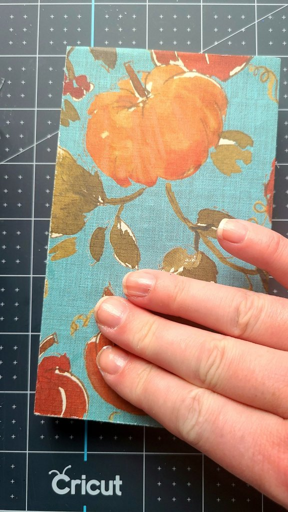 Using my fingers to place cardstock with pumpkins on it on to the piece of wood, and smoothing out any wrinkles and bubbles.