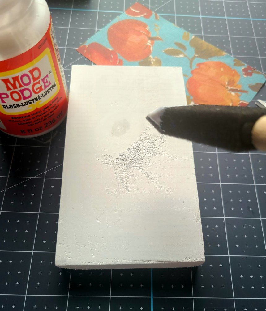 Using a foam brush to paint a layer of Mod Podge on the top of one of the faux reversible books.