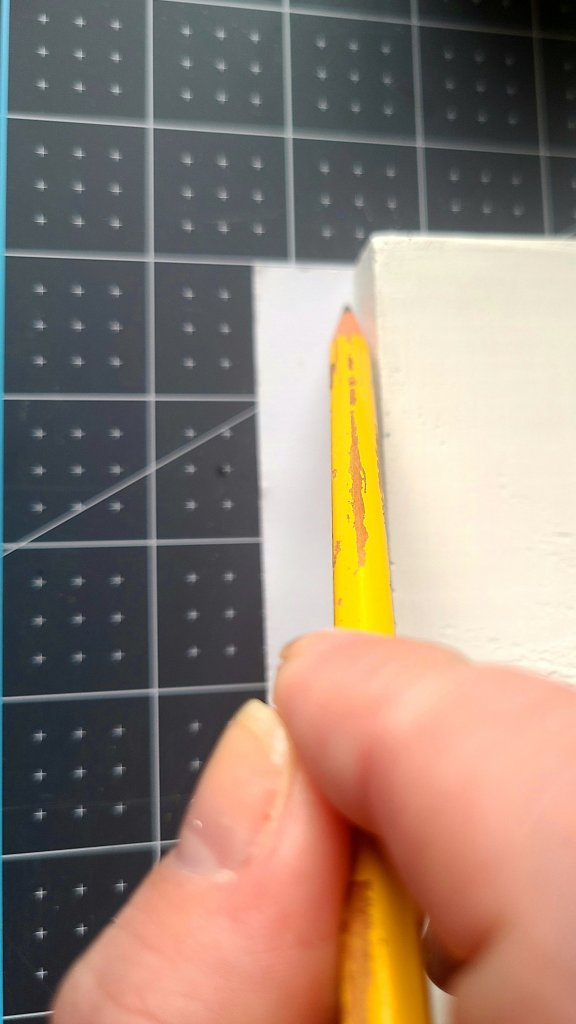 Using a pencil to trace around the wood on cardstock to make a cover for the fall side of the faux reversible books.