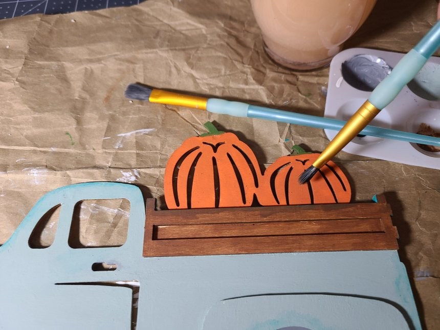 Painting the pumpkins in the bed of the truck orange. This will be glued as the main part of the DIY fall centerpiece,