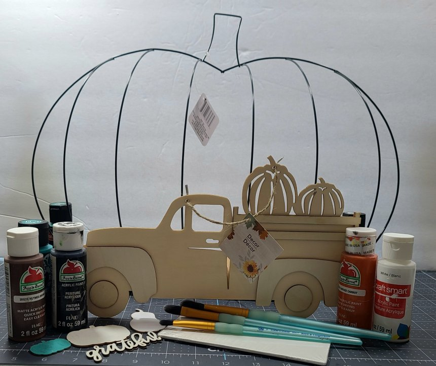 Supplies for the DIY fall centerpiece: pumpkin wire wreath form, wood truck w/ pumpkins in the bed, acrylic paint, paint brushes, & 4x6 canvas.