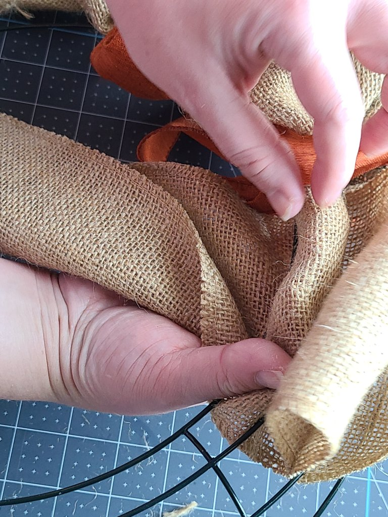 Pulling a piece of burlap ribbon through the inner ring on a wire form on the burlap wreath.