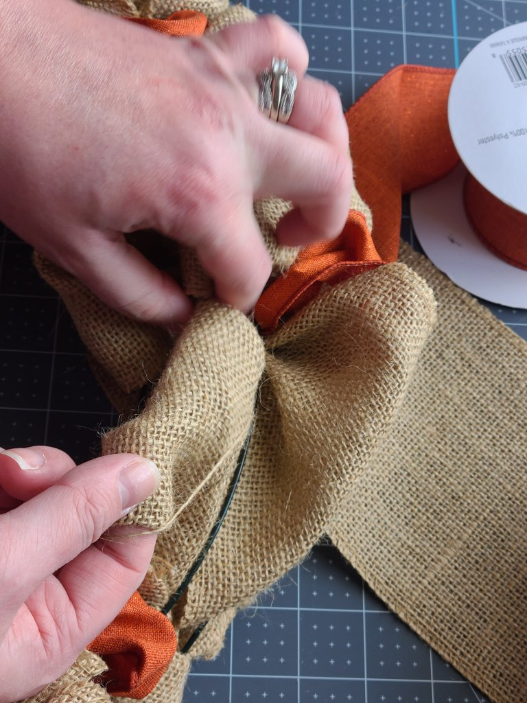 Pulling burlap through the middle ring of the burlap wreath form.