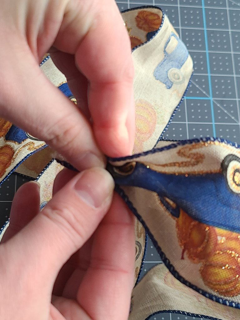 """Pinching the ribbon near the beginning of the roll, about .5"""" from the end, between the thumb and forefinger. This is the first step in how to make a bow for a wreath."""