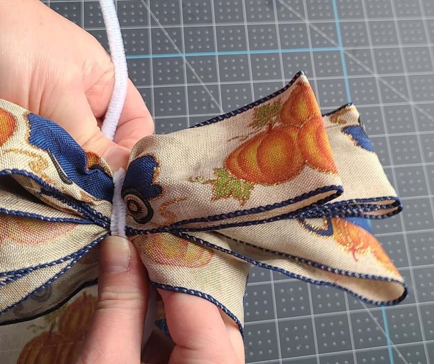 Beginning to wrap the pipe cleaner around the middle of the bow to secure it. This is one of the last steps in the tutorial on how to make a bow for a wreath.