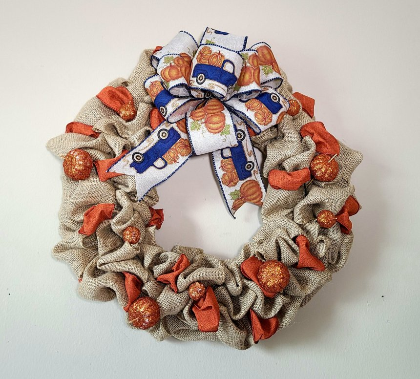 Burlap wreath with farmhouse truck ribbon bow with glitter pumpkins added in.