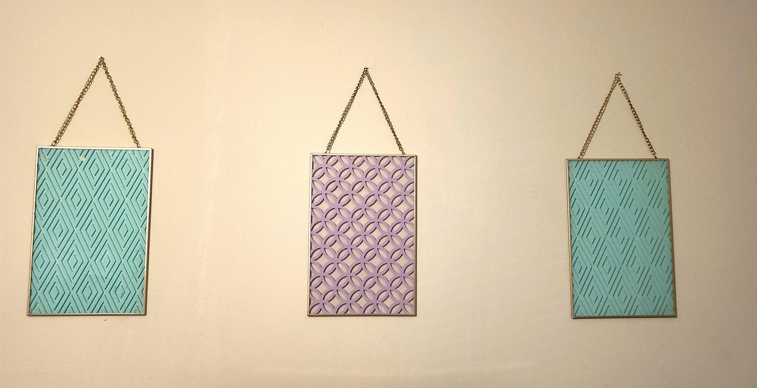 Craft room makeover: glass wall art for the walls. Two aqua with gold rim & chains and one purple with gold rim & chain.