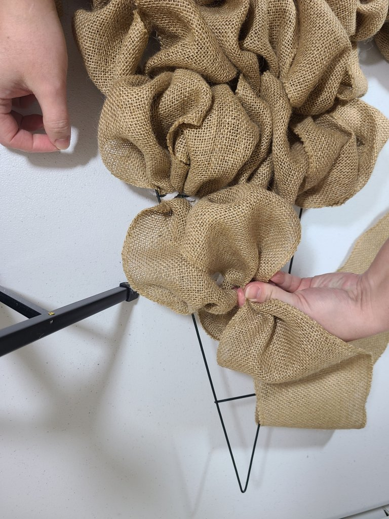 Creating a burlap bubble, pinching the width of a section and attaching it to the burlap witch hat wreath form.