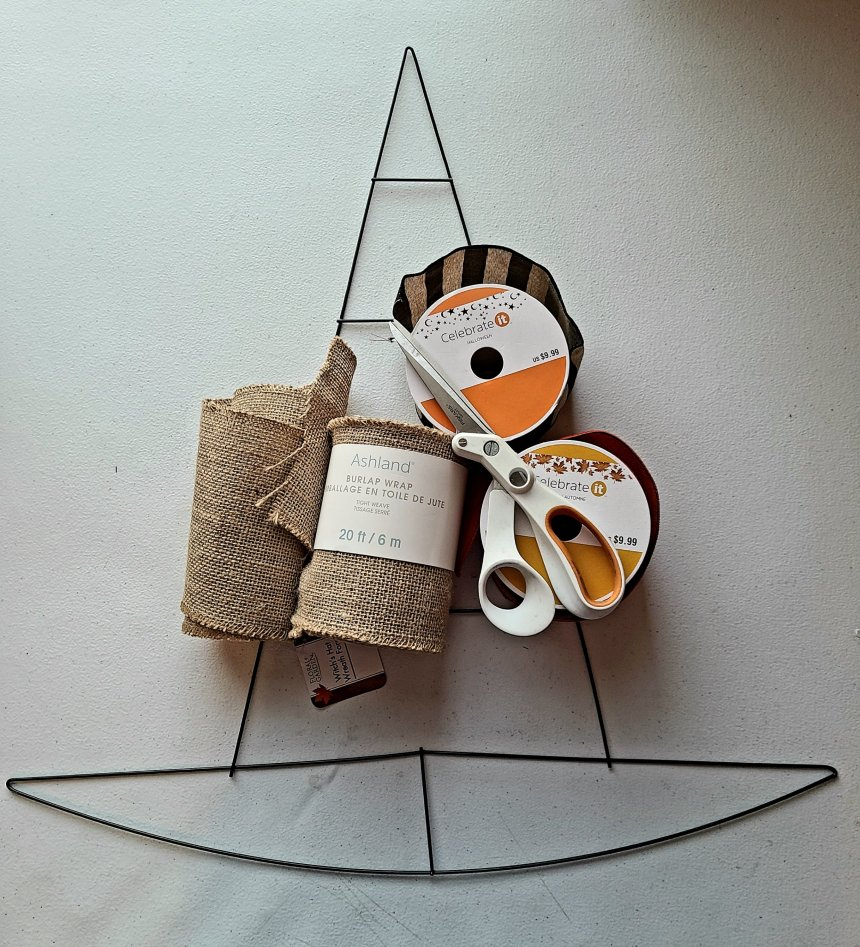 """Supplies for a burlap witch wreath: witch hat wire wreath form, 2 rolls of 5"""" burlap, scissors, two rolls of 2.5"""" wired ribbon."""