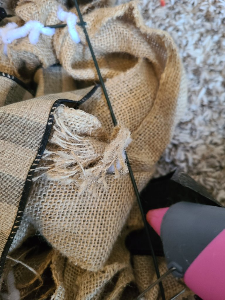Adding a strip of hot glue to the outer wire at the bottom of the burlap witch hat wreath where the triangle meets the brim.
