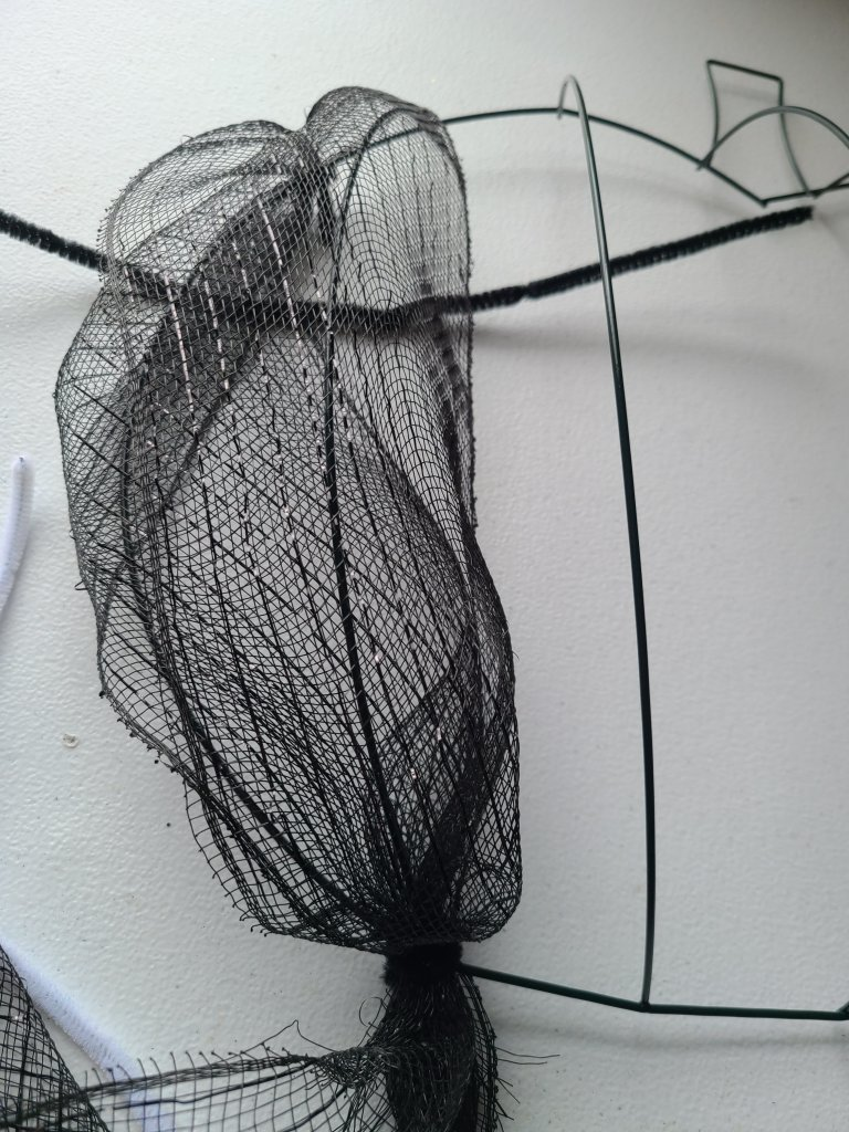 Black deco mesh brought from the bottom of the Halloween pumpkin wreath form up to the top and attached to the left of the first vertical crossbar with a pipe cleaner. This creates a vertical line of deco mesh with some puffiness in the middle.
