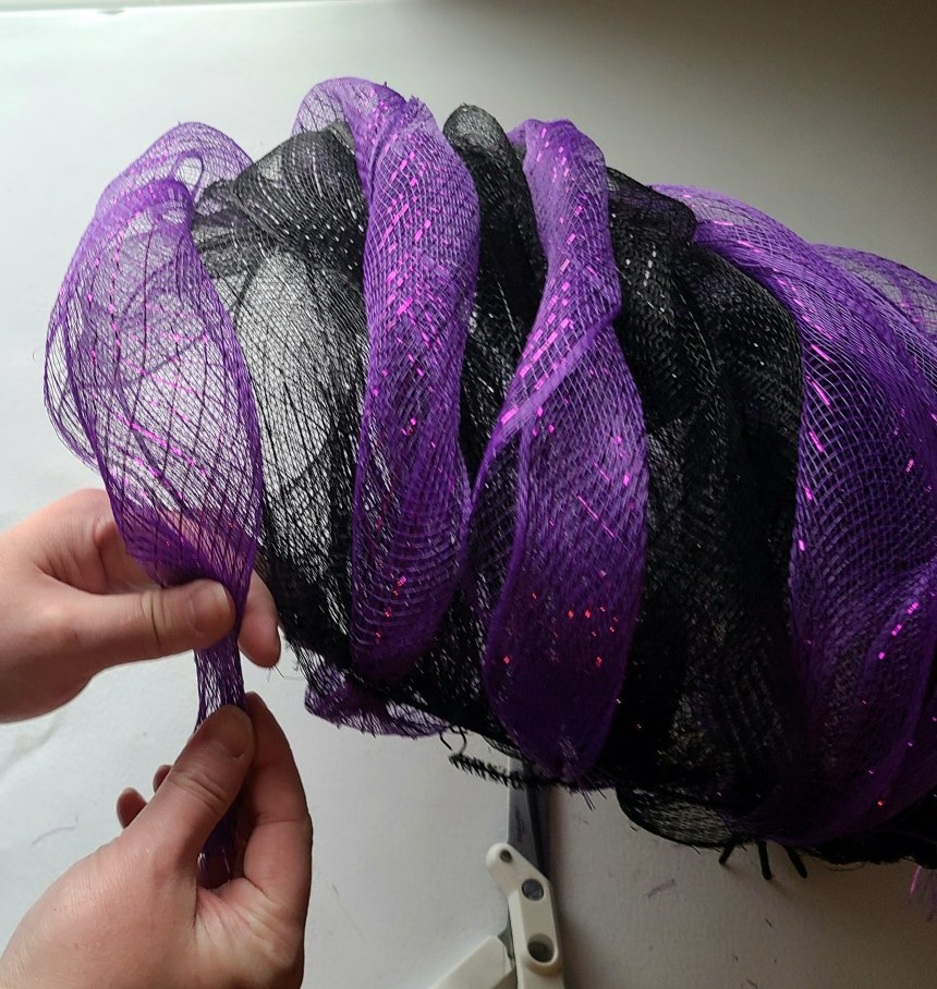 Attaching a deco mesh spiral to the bottom wire of the Halloween pumpkin wreath.