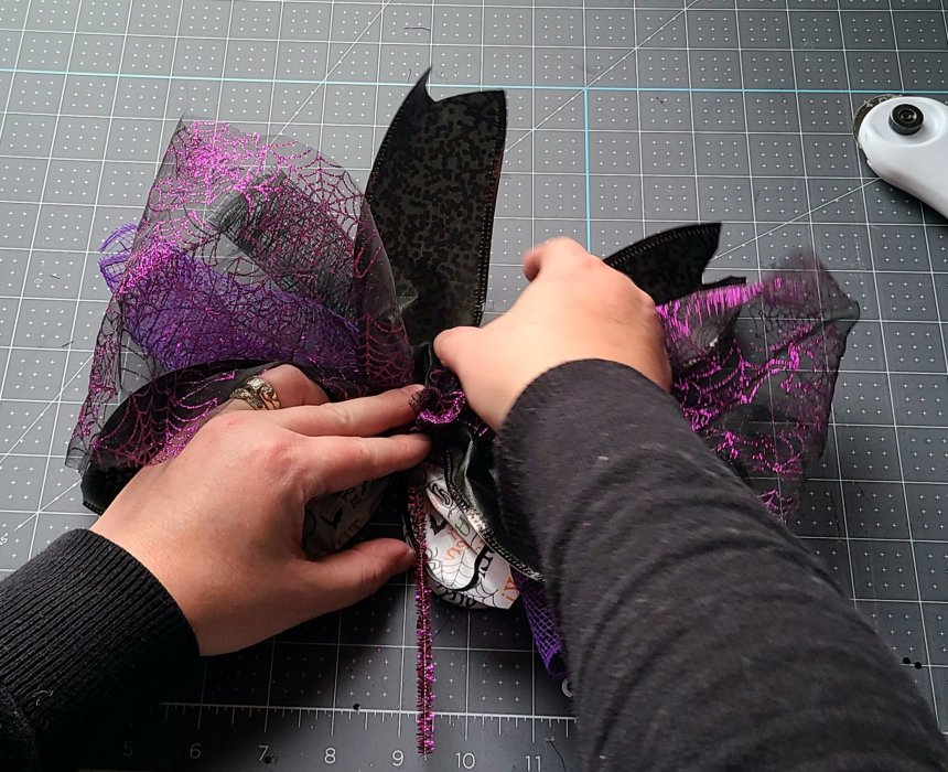 Adding the sheer mesh bow to the back of the bow for the Halloween pumpkin wreath.