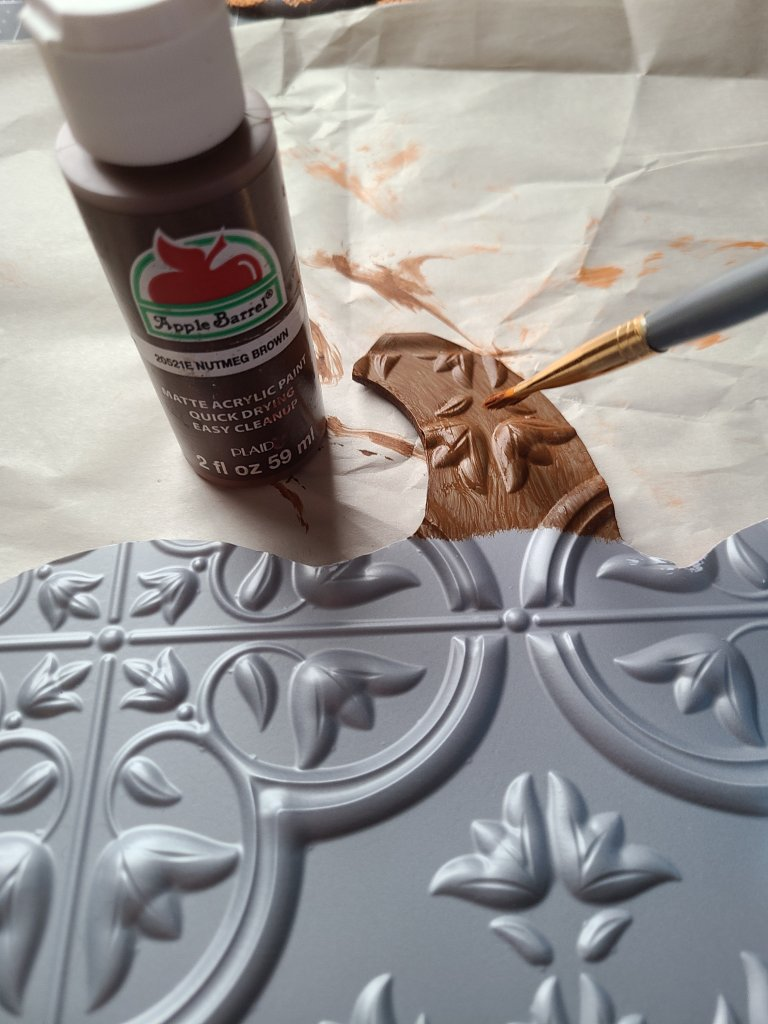 Painting the stem of the fall pumpkin sign with brown acrylic paint.