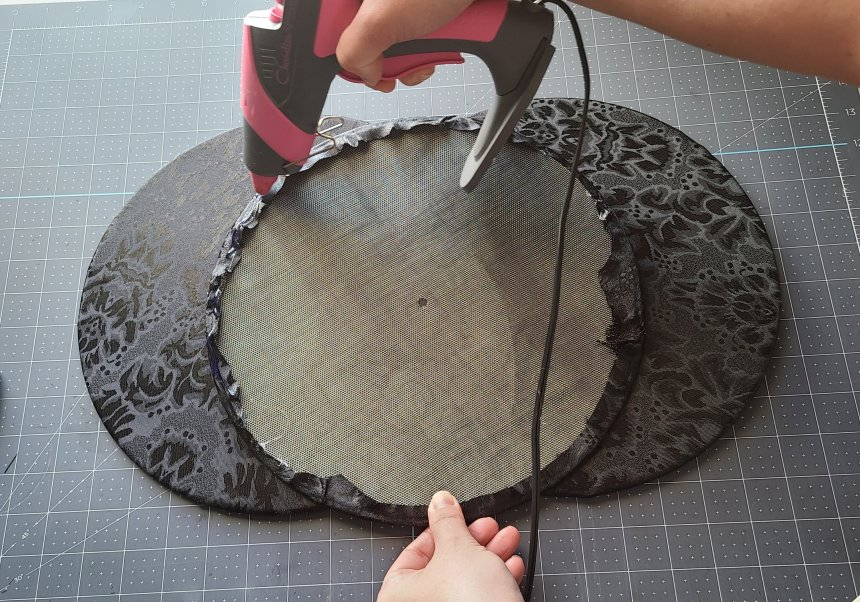 Adding hot glue to the edges of the third splatter screen.