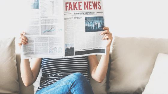 Woman reading newspaper of Fake News