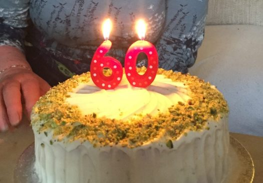 Round courgette and lime cake with 60th birthday candles
