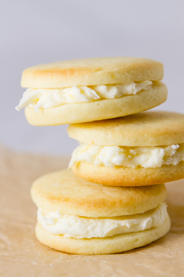 a stack of sandwich cookies on a piece of parchment paper