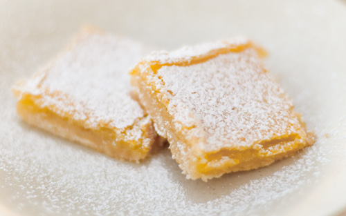 lemon bars on a plate covered in powdered sugar