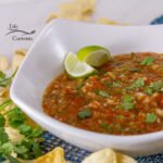 salsa in a white bowl with lime wedges, chips around the bowl.
