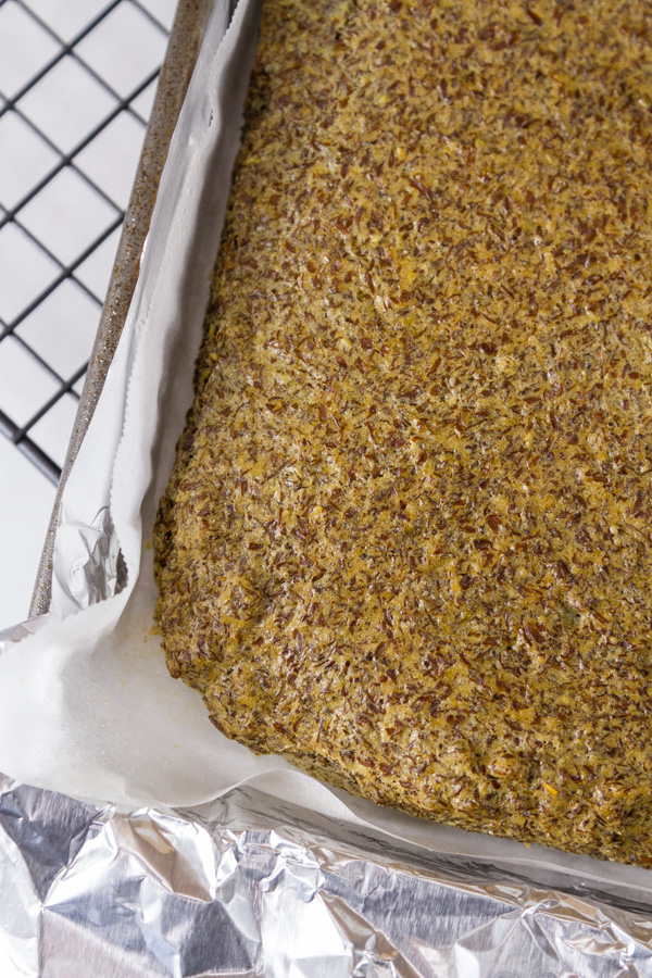for the Gluten-Free Baking & Baked Goods post - Flax Seed Bread in the tray just after baking with parchment paper lining and aluminum foil in the tray all on a cooling rack
