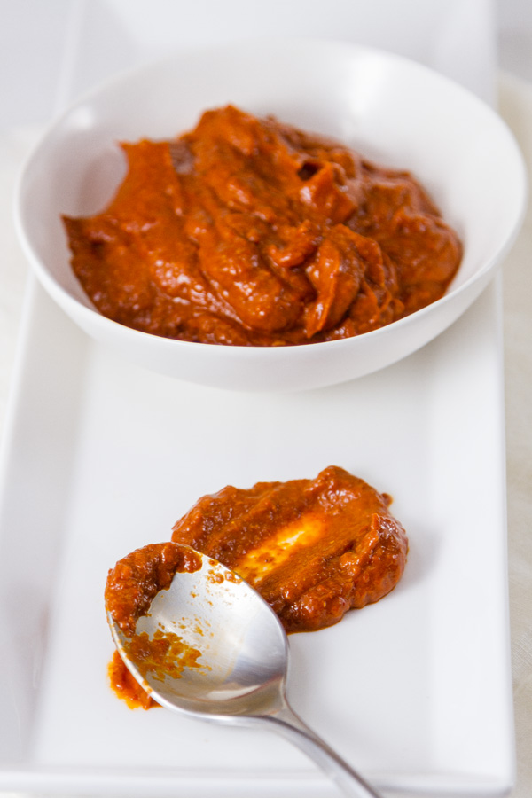 a bowl filled with red spicy paste and a spoon in front of the bowl with a smear of the paste all on a white plate