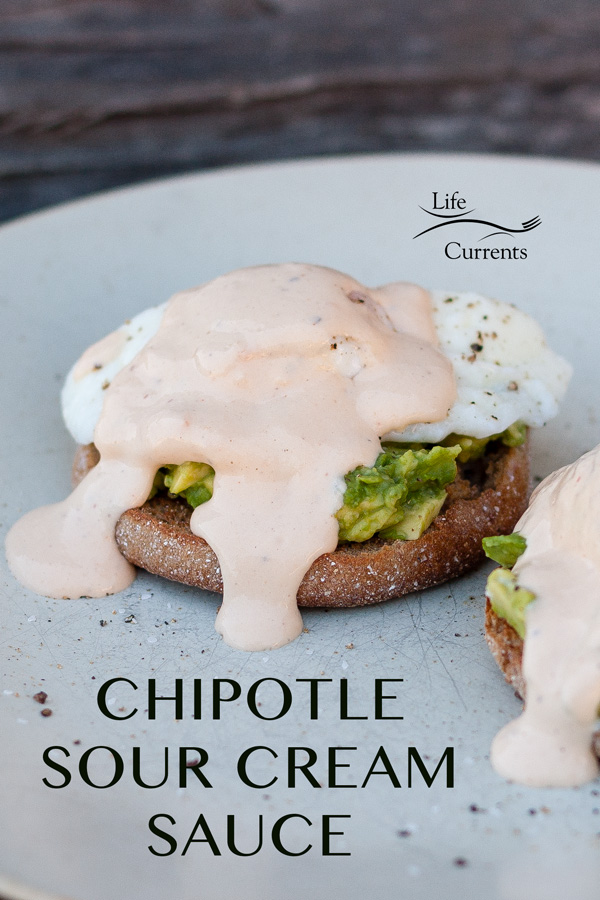 chipotle sour cream sauce over poached eggs, avocado, and english muffins on a white ceramic plate with a wooden background