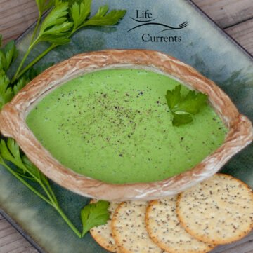 green dressing in a brown bowl on a green plate on a wood background with crackers