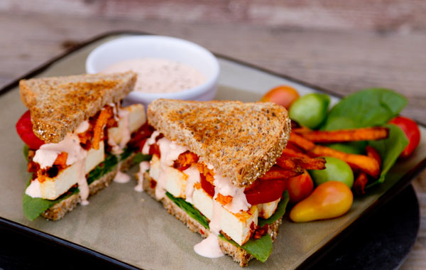 spicy crispy tofu sandwich: With fresh spinach, tomatoes, sweet potato fries, and chipotle-sour cream sauce on toasted sprouted 7-grain bread vegetarian