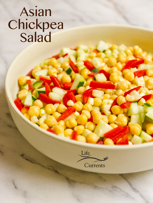 salad with garbanzo beans, corn, red pepper, and cucumber in a large bowl on white marble.