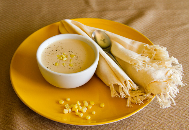 corn soup in a white bowl garnished with corn kernels on a yellow plate and a white napkin and a spoon on a brown table cloth