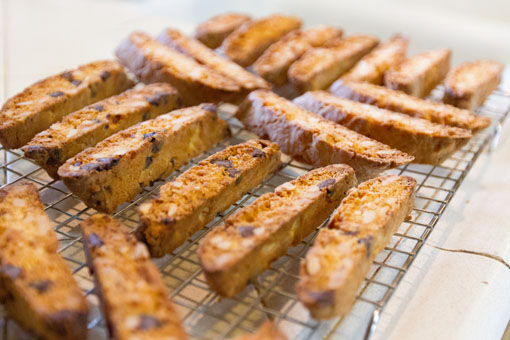 Almond biscotti, all baked and golden brown, cooling on a wire rack