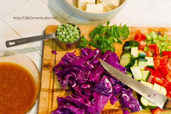 veggies chopped on a cutting board with a knife, sauce in a bowl on the left.